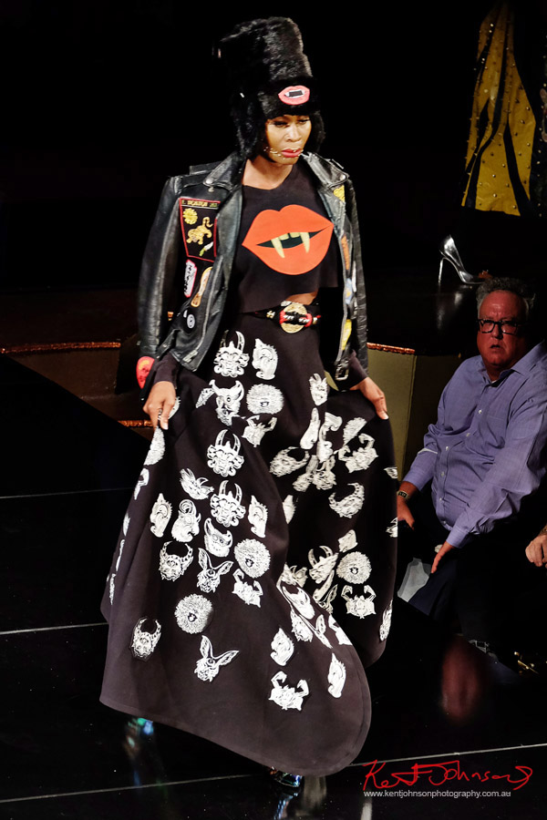 Graphics printed maxi skirt, lips shirt, leather jacket with woven patches, faux fur hat. Dexter Simmons at Art Hearts Fashion NYFW 2017 photographed by Kent Johnson.