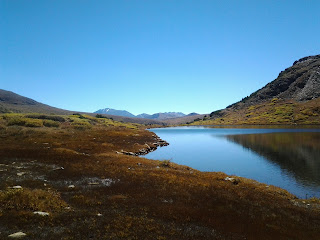 Beautiful sunny fall day in the mountains.  A small mountain lake showing reflections of the mountain in the water.