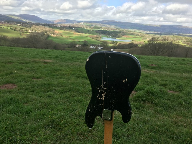 back-of-broken-electric-guitar-planted-in-ground-with-view-over-valley-in-background