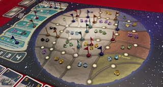 A view of the board in the middle of a game. Gems of various colours have been placed in the spaces on the board, and a number of plastic flags in various colours have been placed on the icons on the borders between the spaces. One flag in each colour remains on the special actions spaces, and one flag of each colour occupies the spaces of the player order track in the top left.