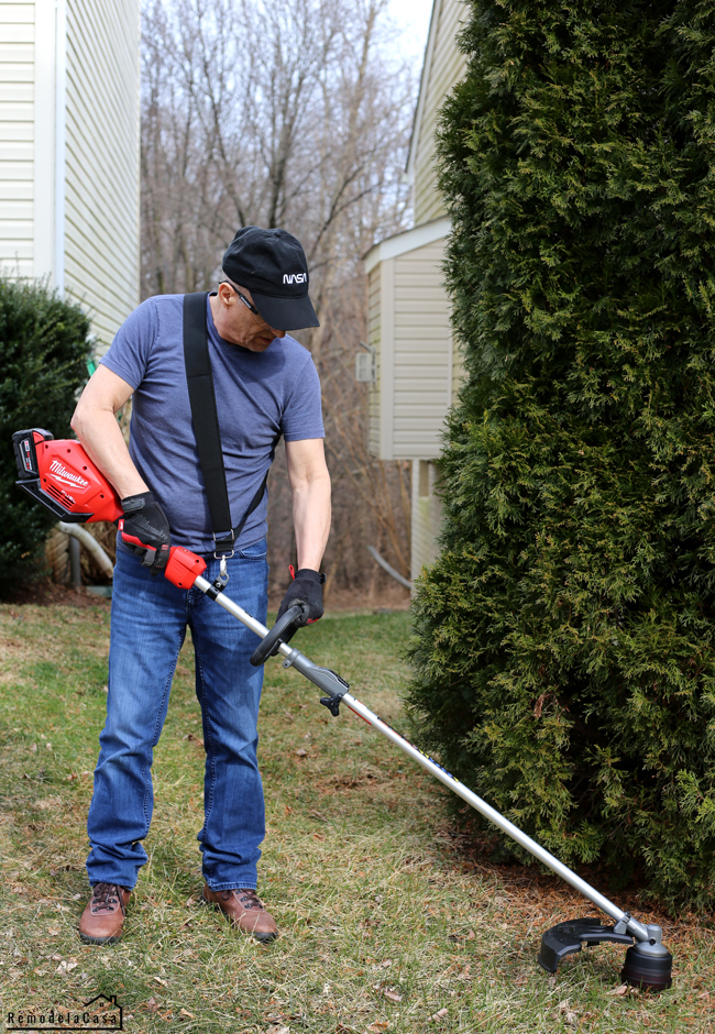 German Garay trimming the lawn with Milwaukee string trimmer
