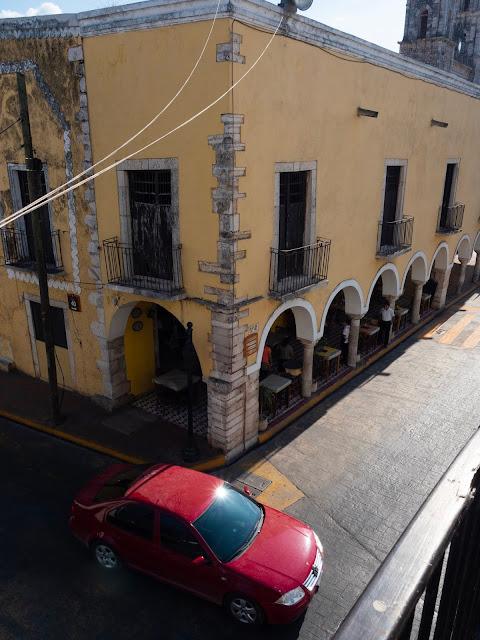 Esquina de una plaza colonial con arcadas y un coche rojo