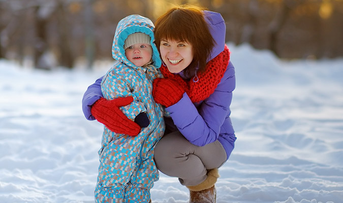 Woman with child outside in the snow