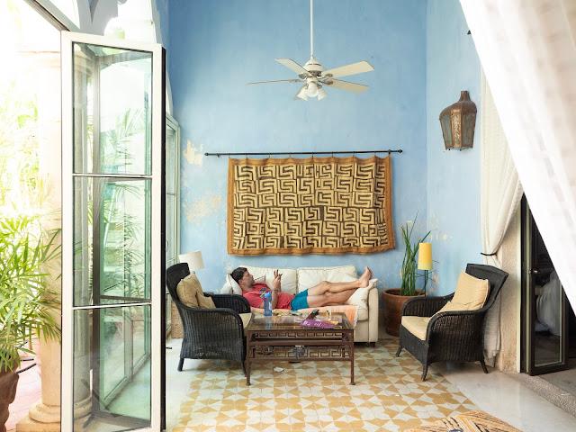 Hombre tumbado en un sofá en una de estar con suelos amarillos y pared azul