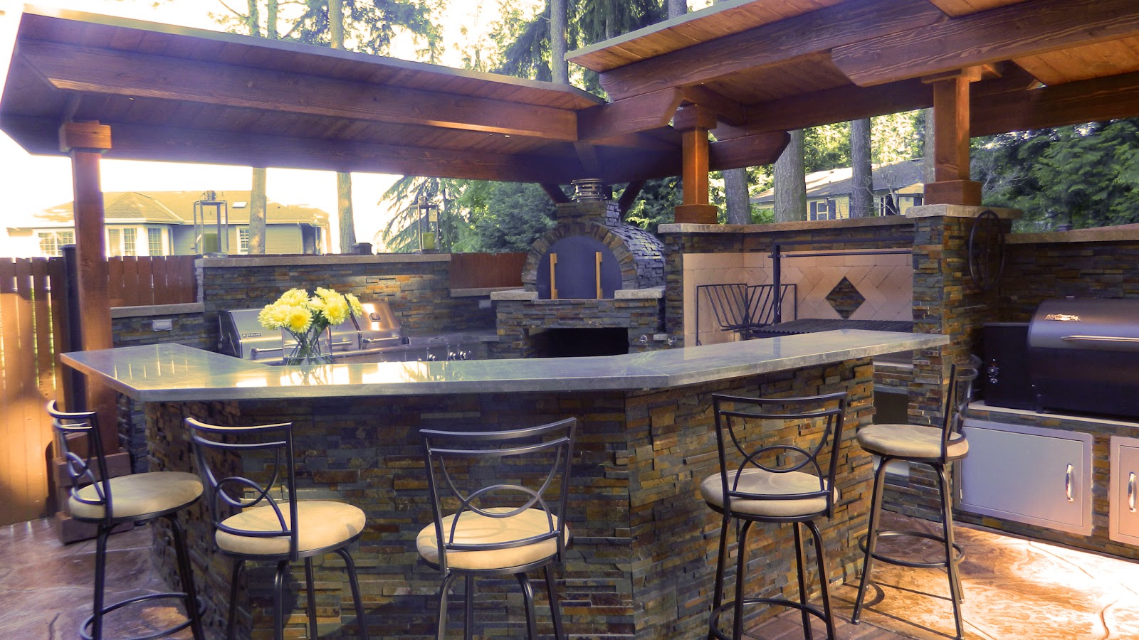 outdoor kitchen with argentinian grill, brickwood pizza oven and