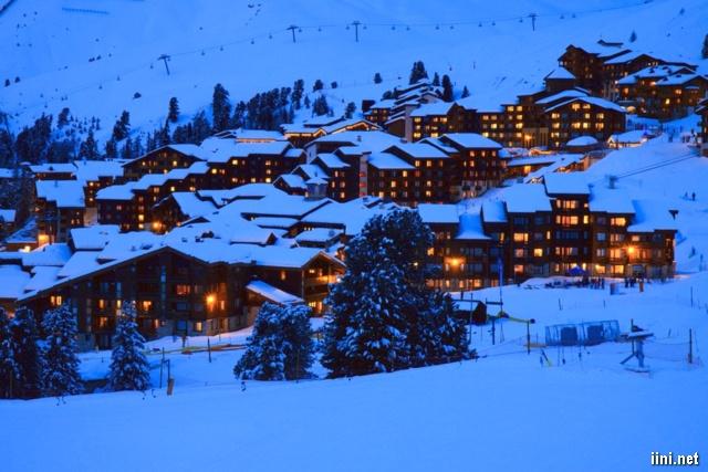 những ngôi nhà sáng đèn trong mùa đông tuyết trắng