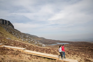 two walkers descending cuilcagh mountain on the boardwalk