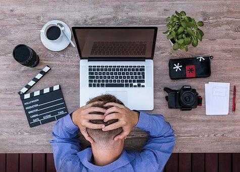 investidor ao computador com as mãos à cabeça pelas perdas