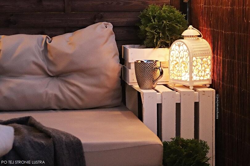 siedzisko z palet, drewniane białe skrzynki i tuje na balkonie