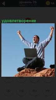 Мужчина на холме с ноутбуком поднял руки вверх и кричит от удовлетворения