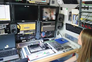 Viele Monitore und Mischpulte übereinander angeordnet. Am rechten Bildrand sitzt Autorin Susanna