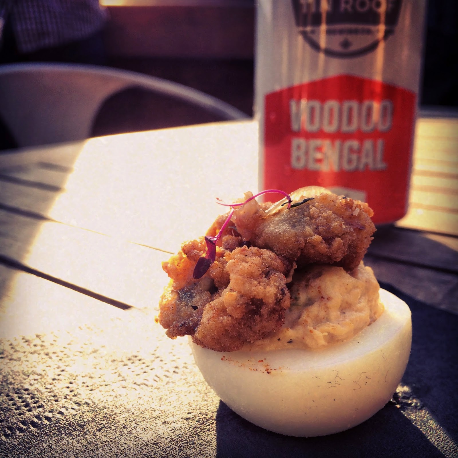 Crawfish & Tasso Deviled Egg topped with a crispy Fried Oyster and Bacon Fennel Jam