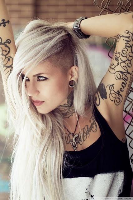 chica rubia de tipo gotica, lleva en los brazos tatuajes de letras y frases