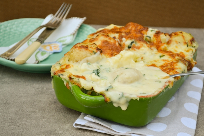 A comforting cauliflower cheese bake with a difference. Cauliflower and waxy baby potatoes in a cheese and spinach sauce topped with mozzarella and baked until golden. Veggie and vegan recipe.