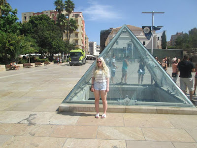 blonde girl in malaga by the glass pyramid