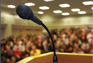 Photo of a microphone at a speaker's podium with a blurred audience in the background.