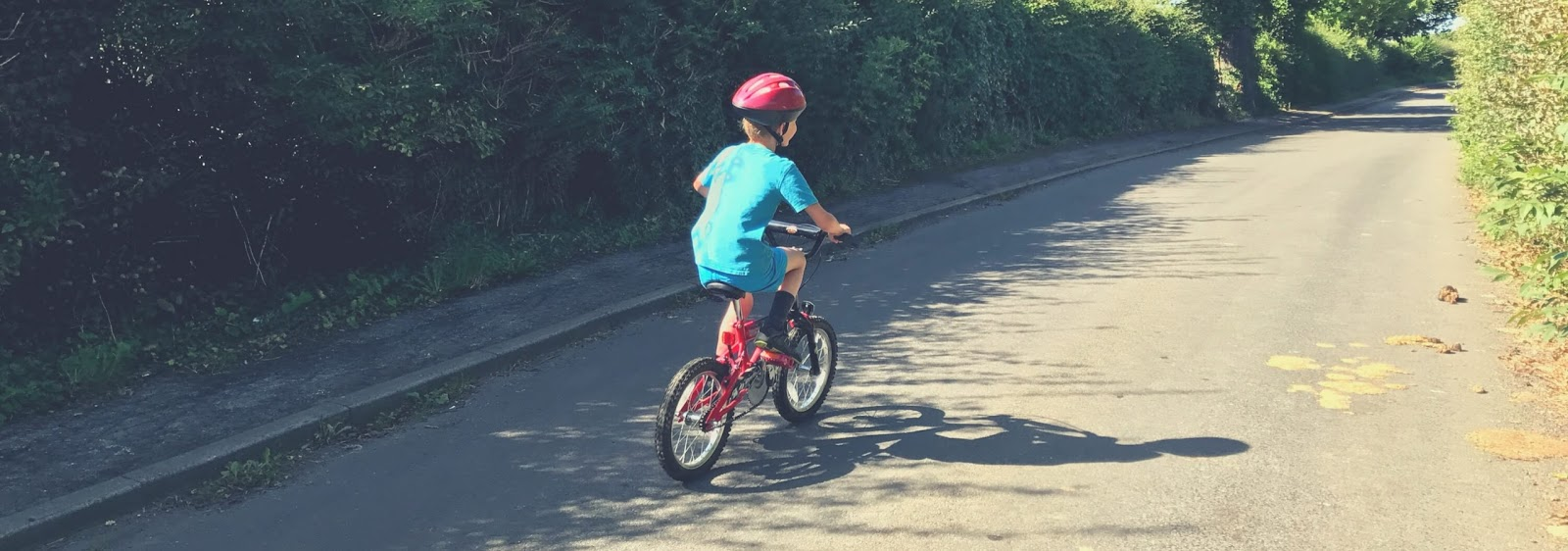 8 year old boy on a red bike riding on a road