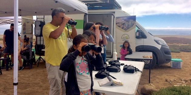niñas y adulto con binoculares observan aves de Humedal Los Choros