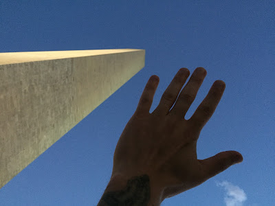 looking up at washington monument with hand