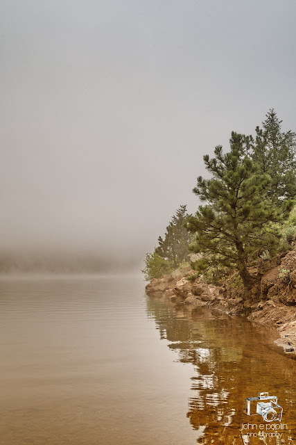 a foggy day on a reservoir in the Colorado mountains, with reflections of the waters edge in the calm waters