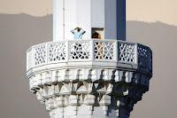 Büyük bir minare şerefesinde ezan okuyan bir müezzin çizimi