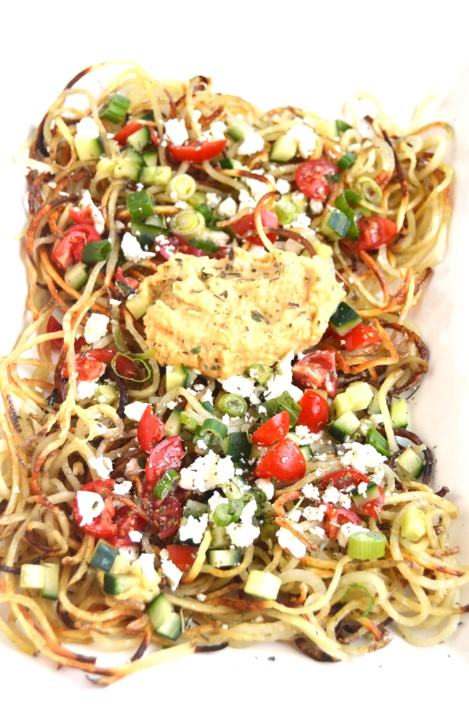 Greek Spiralized Fries are crispy, flavorful and loaded with your favorite toppings including cucumber, hummus, tomatoes, feta cheese and green onions! www.nutritionistreviews.com