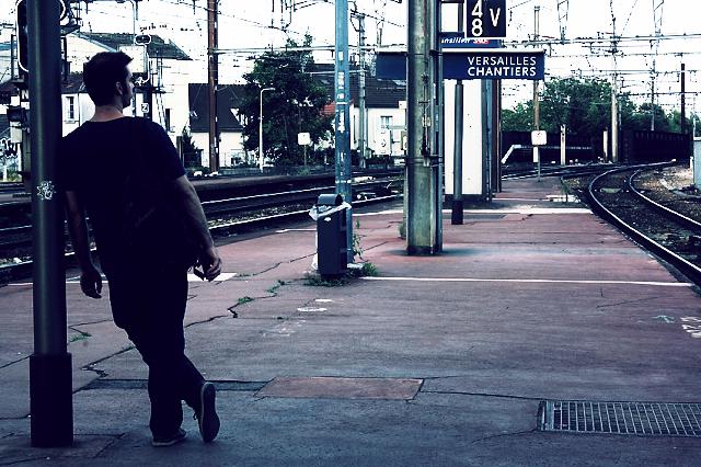 homme sur un quai de gare adossé à un poteau regardant les voies ferrées