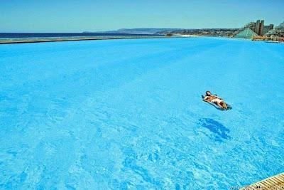 Homem relaxando, flutuando no meio da piscina
