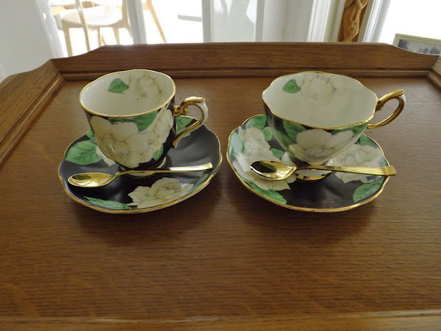 A Demite Coffee Cup To The Left And Tea Right With Regular Spoons In Gold Plate When I Mean