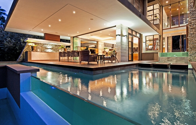 View of the pool and terrace with lights on in the Contemporary South African SGNW House by Metropole Architects