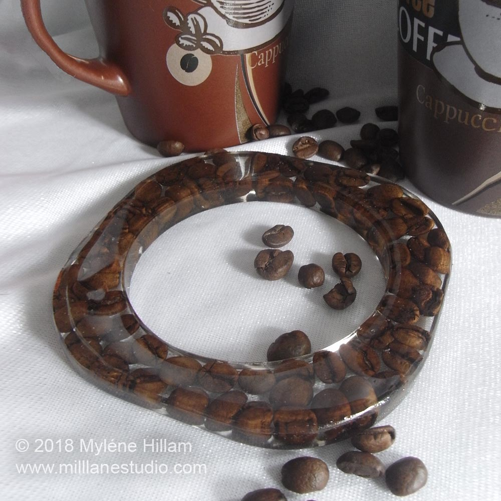 Cast a square epoxy resin bangle with roasted coffee beans.