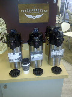 Display with Intelligentsia Coffee sign and 3 coffee dispensers