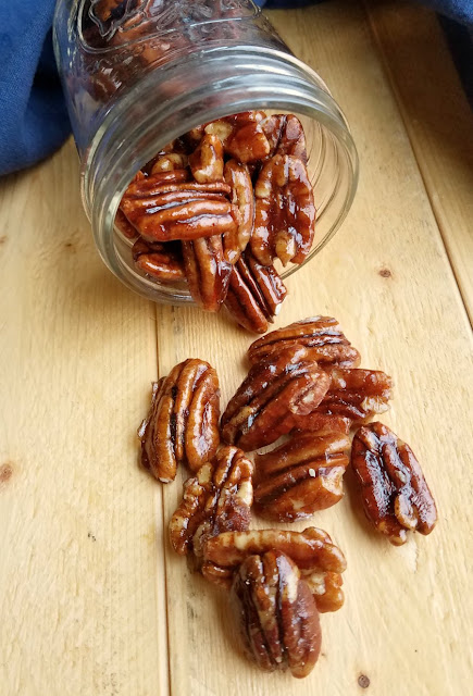 shiny caramel coated pecans spilling out of jar