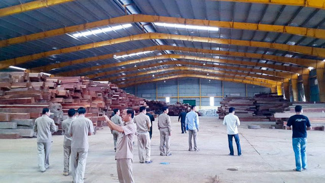 Authorities walk through a rosewood warehouse in Tbong Khmum province during a government crackdown on illegal logging earlier this year. Photo supplied