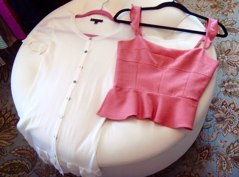 White short sleeve button down and pink sleeveless tops laid on ottoman.