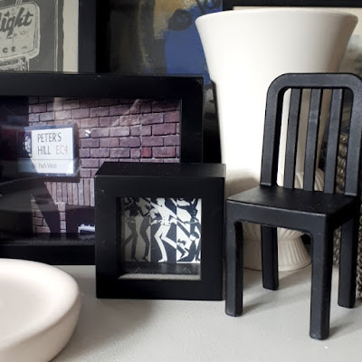 Miniature black chair on display amoungst a selection of framed pictures and white ceramic pieces.