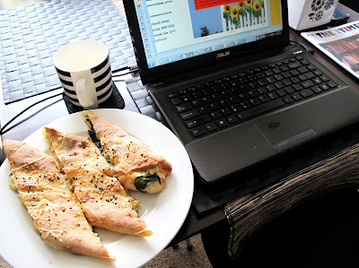 Laptop computer with, on the left, a plate of turkish pide and a mug and, on the right, a biscuit tin and a copy of the magazine The tiny Times.