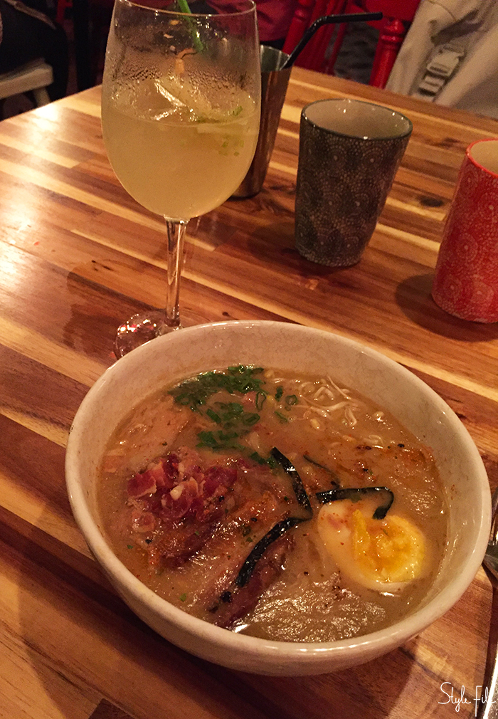 Image of pork belly ramen with eggs with a cocktail in a wine glass on a wooden table