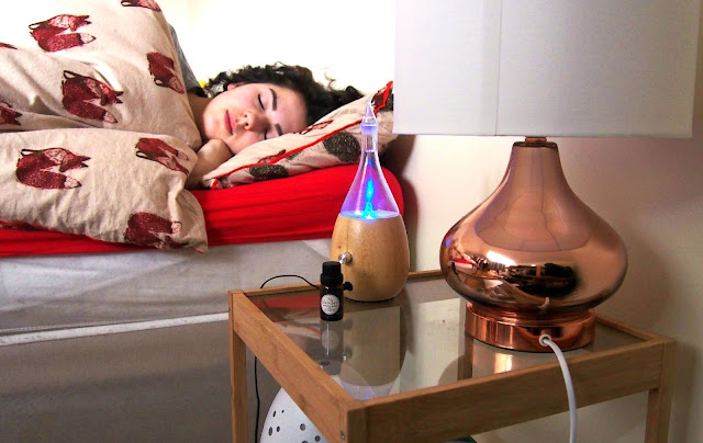 Girl sleeping in bed, diffuser next to bed