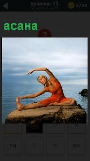 Удобное и устойчивое положение тела в йоге асана, которую выполняет девушка на высоком камне, на фоне воды