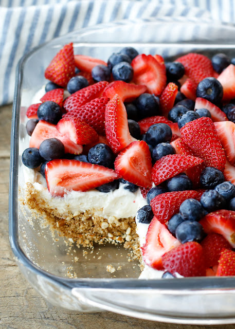 Crunchy pretzels and a creamy filling are topped with piles of strawberries and blueberries making this Berry Pretzel Dessert a favorite dessert for summer! get the recipe at barefeetinthekitchen.com
