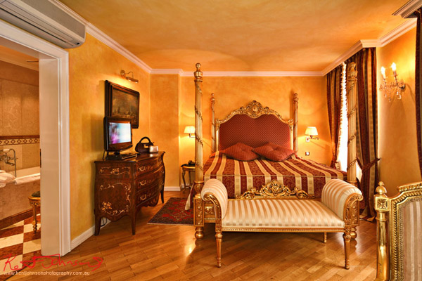 Room interior, suite with four poster bed and antique furniture. Boutique Hotel photography in Prague by Kent Johnson.