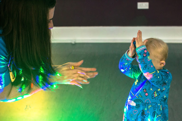 An adult and a child playing with play doh with disco lights on