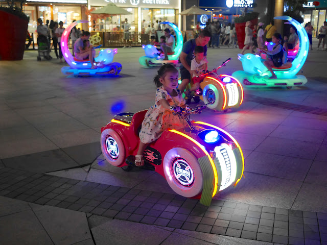 little girl riding an electric toy vehicle at night in Zhongshan, China