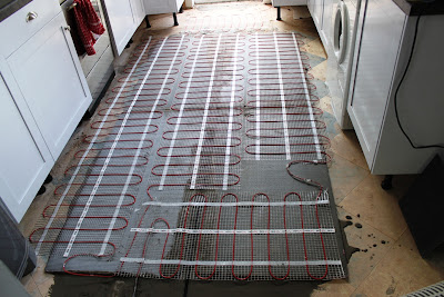 Adding the underfloor heating on top of the insulation boards.