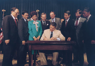President Reagan signs the bill in an official ceremony. Left to right: Hawaii Sen. Spark Matsunaga, California Rep. Norman Mineta, Hawaii Rep. Pat Saiki, California Sen. Pete Wilson, Alaska Rep. Don Young, California Rep. Bob Matsui, California Rep. Bill Lowery, and JACL President Harry Kajihara. Wikimedia.