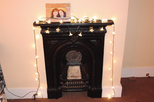 a fireplace with fairy lights draped over it, with a photoframe perched on top