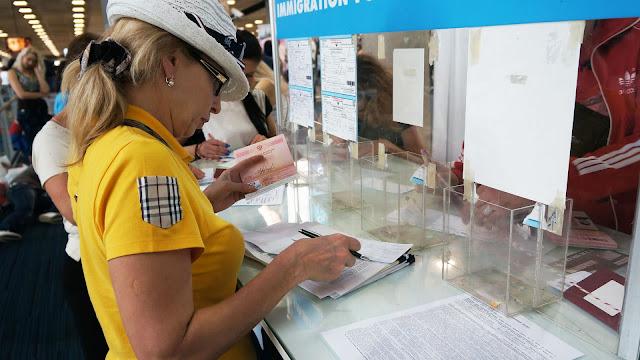 На фото - процедура заполнения миграционной карты в аэропорту
