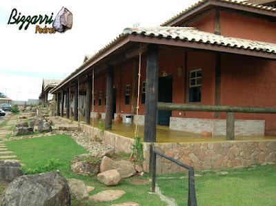 Alicerce com pedra moledo, na construção rústica, com os pilares de madeira, o piso de cimentado queimado amarelo e a cobertura com telha colonial mesclada.