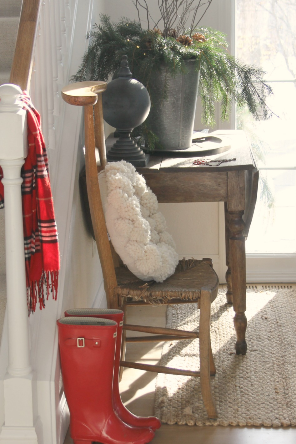 Holiday vignette with red wellies and plaid scarf with vintage chair and wooly wreath. Come be calmed by How to Freak Less About Holidays, Decorating and Gifts as well as Entertaining.